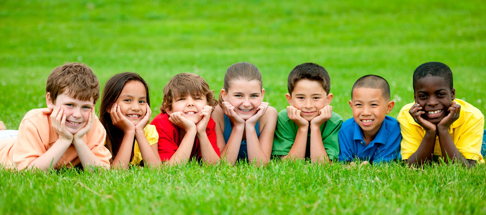 Kids in grass smiling